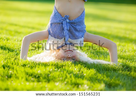beautiful blond girl standing on her head - stock photo