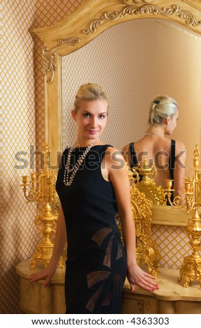 Beautiful blond girl stands near the mirror - stock photo