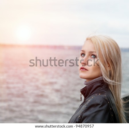 Beautiful blond girl stands near the river - stock photo