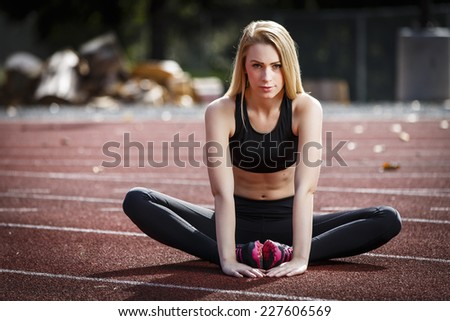 Beautiful blond girl streching her legs on the running track - stock photo