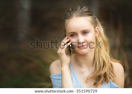 Beautiful blond girl talking on cell phone - stock photo
