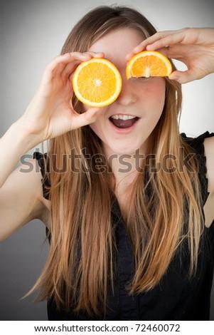 beautiful blond girl using orange as eyes and smiling - stock photo