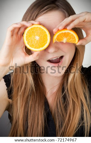 beautiful blond girl using orange as eyes and smiling with a quater orange - stock photo