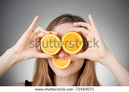 beautiful blond girl using orange as glasses and smiling with a quater orange