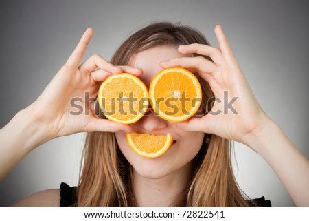 beautiful blond girl using orange as glasses and smiling with a quater orange - stock photo