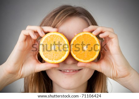 beautiful blond girl using orange as glasses, with grey background