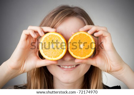 beautiful blond girl using orange as glasses, with grey background - stock photo