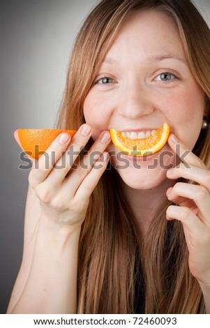 beautiful blond girl using orange as  smiling - stock photo