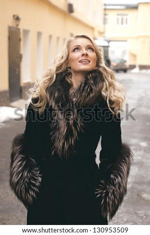 Beautiful blond girl wearing winter coat on the street back yard background - stock photo