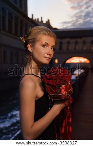 Beautiful blond girl with a bouquet of roses at sunset time near the river