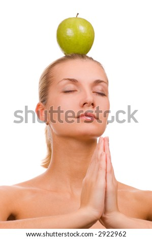 Beautiful blond girl with a green apple on her head - stock photo