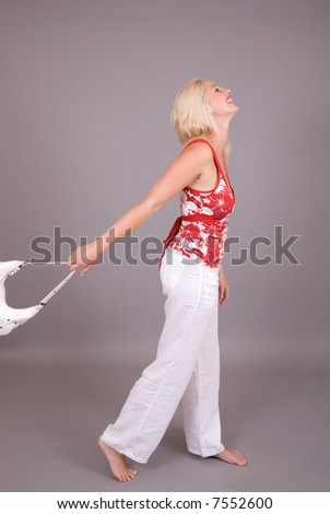 Beautiful blond girl with a happy smile swinging her handbag - stock photo