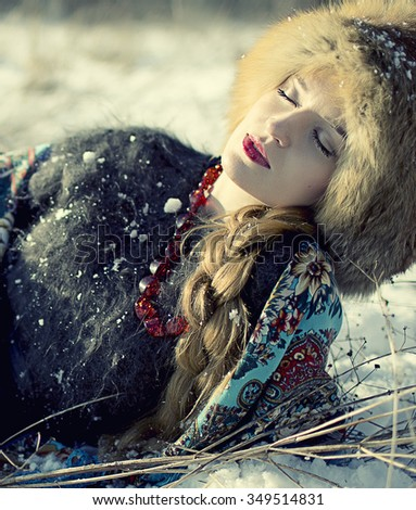 beautiful blond girl with a long braid on a snow landscape