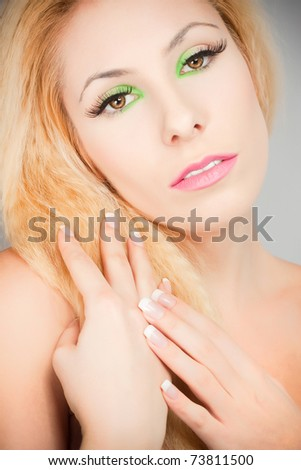 Beautiful blond girl with cat eyes make-up in green - stock photo