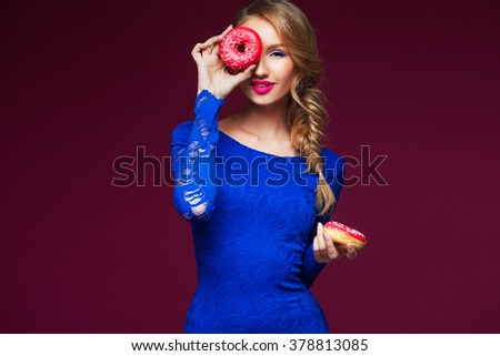 Beautiful blond girl with colorful doughnuts - stock photo