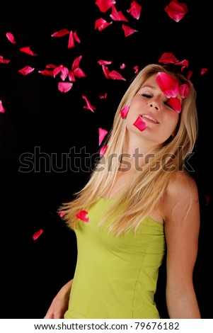 Beautiful blond girl with falling roses petals - stock photo
