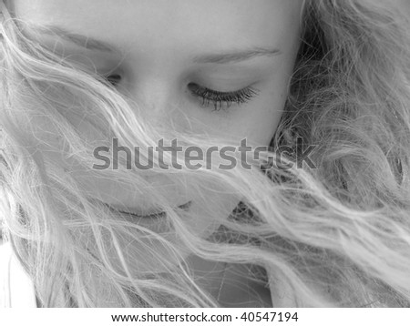 Beautiful blond girl with locks flowing around her face - stock photo