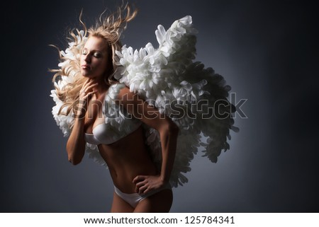Beautiful blond girl with white wings on black background - stock photo