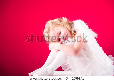 Beautiful blond hair angel on a red background - stock photo