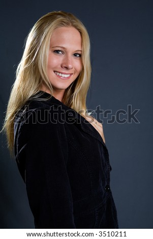 beautiful blond hair blue eyes woman wearing black blazer jacket with a nice smile standing on white