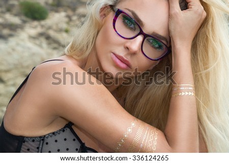Beautiful blond hair sexy woman young girl model in sunglasses and elegant black sexy swimsuit lingerie with crystals around the pool with a balustrade overlooking the sea and the island of Santorini - stock photo