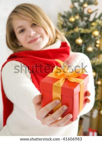 Beautiful blond hair teenage girl in red comforter holding  red gift box with golden ribbon - stock photo