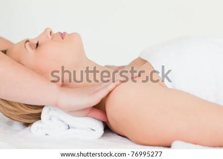 Beautiful blond-haired woman lying down while receiving a spa treatment