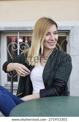 Beautiful blond haired young woman sitting in the sidewalk cafe smiling and  looking away . - stock photo