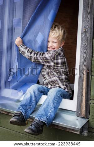 Beautiful blond kid sitting on window sill. Outdoor portrait   - stock photo