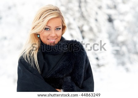 Beautiful blond lady in fur coat in winter forest - stock photo