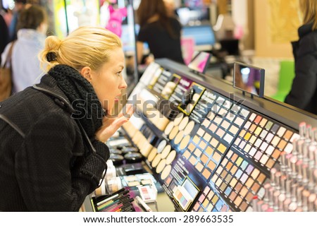 Beautiful blond lady testing  and buying cosmetics in a beauty store. - stock photo
