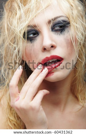 Beautiful blond lady with strange makeup smearing lipstick. Artistic colors added - stock photo