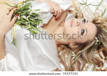 Beautiful blond lies on the white into the flowers - stock photo