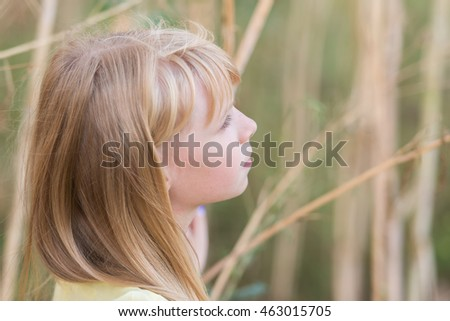 Beautiful blond little girl (model girl) stands on a meadow midst of dried reeds in a beautiful yellow dress