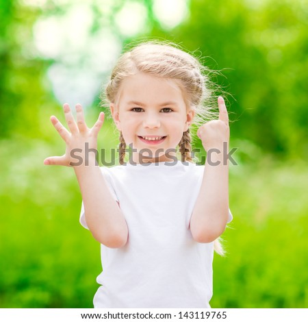 Beautiful blond little girl showing six fingers (her age) and smiling - stock photo