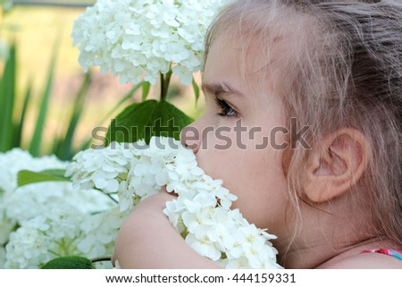 Beautiful blond little girl smelling big white flowers on the bush, outdoor portrait - stock photo