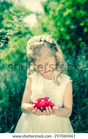 beautiful blond little girl with flower headband holding red rose held in hands - stock photo