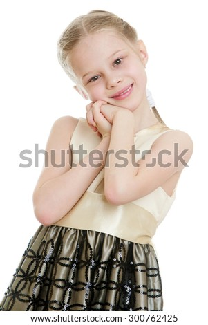 Beautiful blond little girl with long silk dress. The girl placed her hands on his chest near the face and smiles sweetly at the camera, close-up-Isolated on white background - stock photo