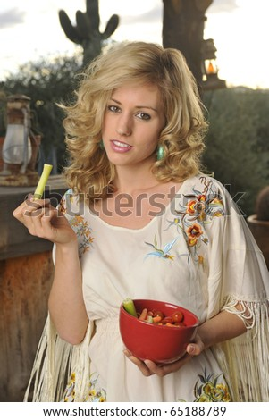 Beautiful blond model eating healthy vegetable snack at home on patio in rural Southwestern USA scene. - stock photo