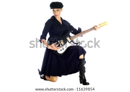Beautiful blond model kneeling playing guitar in black dress and hat