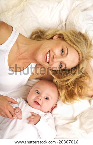 Beautiful blond Mother and her bay lying together with big smiles