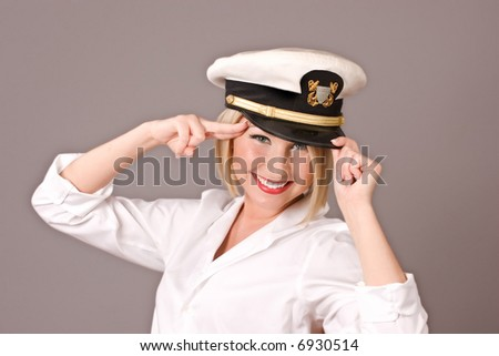 beautiful blond navy pinup girl with officers hat saluting, room for copy - stock photo