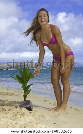 beautiful blond on beach with coconut palm - stock photo