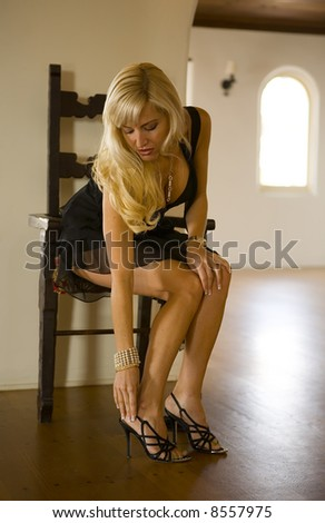Beautiful Blond sitting in a chair fixing her shoe. - stock photo