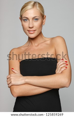 Beautiful blond smiling at the camera with folded arms wearing black top over gray background