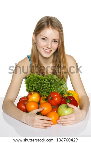 Beautiful blond smiling girl embracing vegetables and fruits over white background