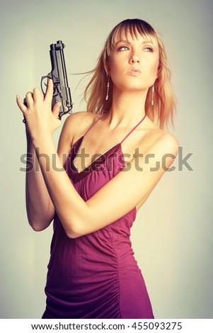 Beautiful blond spy, woman holding gun - stock photo