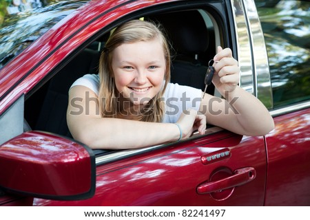 Beautiful blond teenage girl sitting in her new car, holding the keys. - stock photo