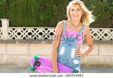 Beautiful blond teenager girl smiling, standing in a suburban street holding a skateboard on a sunny weekend, outdoors. Adolescent lifestyle and sporty living activities, sunshine in home exterior.