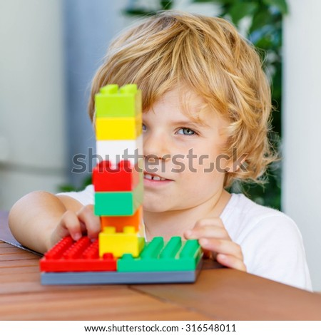 Beautiful blond toddler child playing with lots of colorful plastic blocks indoor. Active kid boy having fun with building and creating. - stock photo